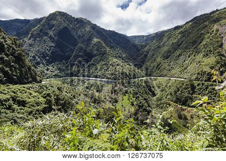 Highway to the coast on a sunny day built at the foot of rain forest in the foothills of the western cordillera of Ecuador