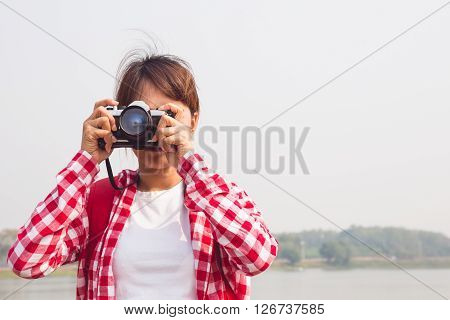 young woman girl is travel with backpack and handle camera of take photos. travel concept
