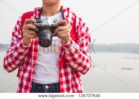 young woman girl is travel with backpack and handle camera and check photos. travel concept