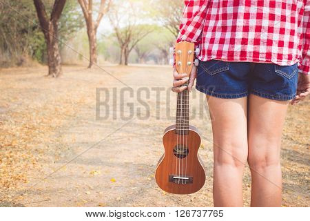 Beautiful asian women holding ukulele guitar at outdoor