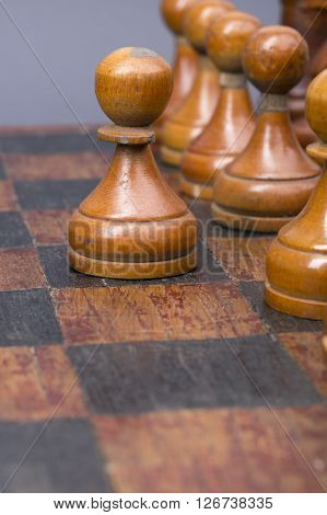 row of vintage wooden pawns on chessboard with focus on started one