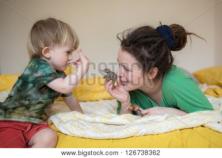 Mom with dreadlocks and her little son playing on the bed with the figures of animals (elephant giraffe) lifestyle real interior the concept of family lazy weekend morning with children