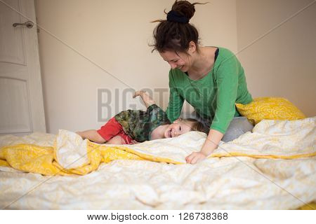 Young mother with dreadlocks with her 2 years old little son are relaxing and playing in the bed at the weekend together lazy morning warm and cozy scene. warm light colors selective focus.