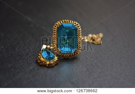 ring and necklace golden accompanied by a precious stone