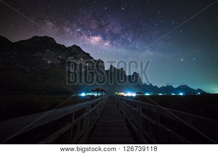 Milky way with wooden walkway at the lake, night sky landscape.