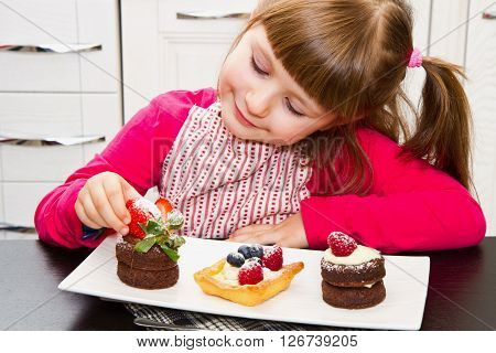 a smiling little girl preparing cake with fruit