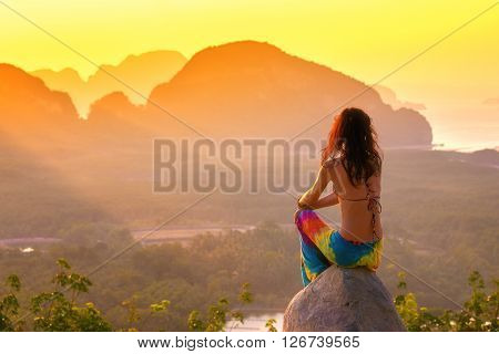 Rear view of woman sitting on the rock seeing the view of Phang nga island, Thailand. Travel concept.