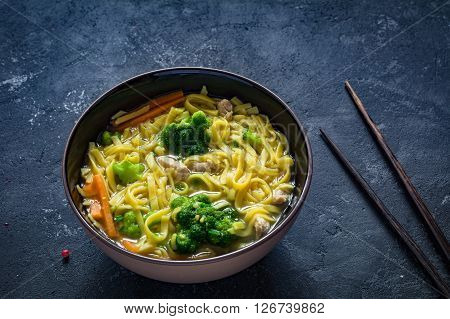 Asian noodle soup Ramen with vegetables and pork in bowl and chopsticks on textured background