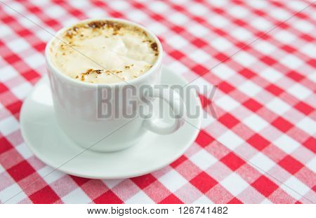 Black coffee with rich crema in a white porcelain cup on a background of red and white checkered cloth ** Note: Soft Focus at 100%, best at smaller sizes