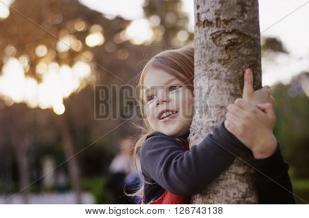Beautiful little girl smiling hugging a tree trunk. Little girl playing in the park
