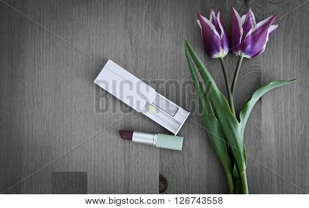 Tulips, lipstick and eye shadows. Two purple tulips and cosmetics on decoloured wooden background. Small bouquet of tulips. Cosmetics and flowers. Two violet tulips