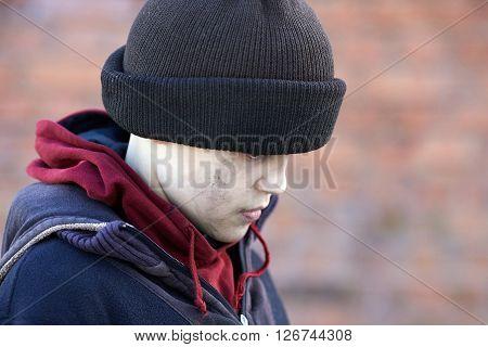 dramatic portrait of a little homeless boy poverty city street