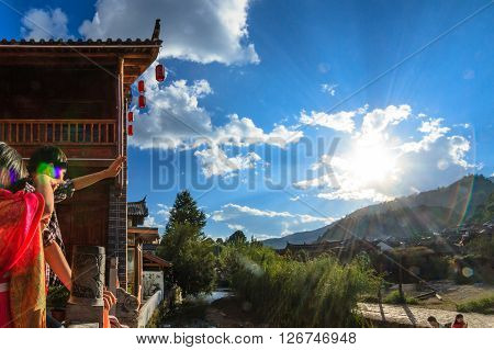 Lijiang, China - October 3, 2014: A Chinese tourist couple watches the traditional village in front of mountain scenery.