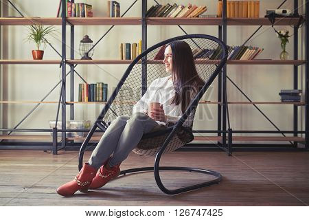 Girl sits in a chair with a cup and looking to the side