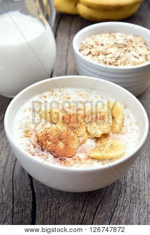 Healthy breakfast oats porridge with banana slices and cinnamon