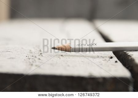 Homework idea. A pencil on the table, homework inscription in pencil. ** Note: Shallow depth of field