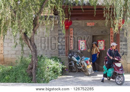 Lijiang, China - Oct 04, 2014: Two local people stand and sit on motorbike in front of gate of Chinese traditional architecture in Shuhe, Lijiang old town in Yunnan province, China