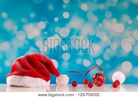 Red Santa hat on blue snowy backgroung