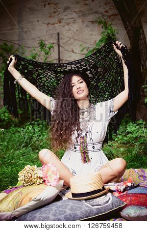 smiling young woman in boho style clothes sit in garden on grass with arms open holding crocheted scarf full body shot