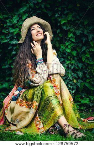 smiling young woman in silky boho style dress and  hat sit in garden summer day full body shot