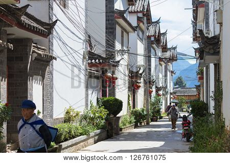 Lijiang, China - Oct 04, 2014: People walk through a street amidst Chinese traditional architecture in Shuhe, Lijiang old town in Yunnan province, China