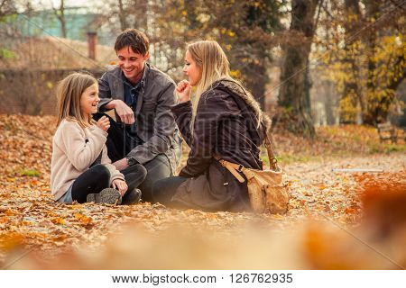 ZAGREB, CROATIA - 15 NOVEMBER 2015: Cheerful family of three kneel on park ground covered with leaves on an autumn day.