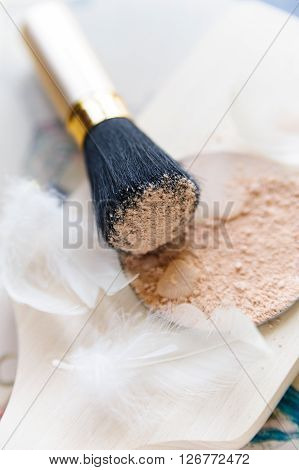 Close-up of mineral face powder with drops of water and brush