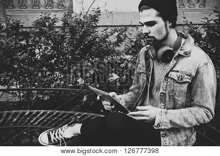 man holding a tablet and thinking in the street