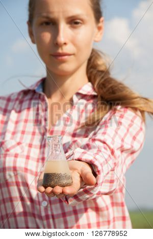 Water Purity Test. Woman holding a chemical flask with water.
