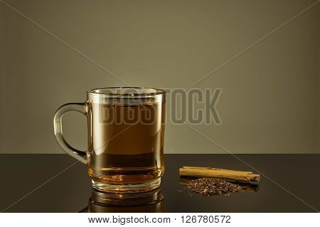 Cup of rooibos tea with lose tea and cinnamon beside of cup. Brown filter used for warmer atmosphere.