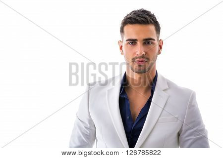 Handsome young man in blue shirt and white jacket posing isolated on white background in studio
