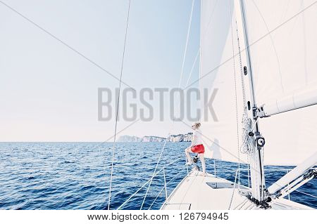 Young woman wearing sunglasses and red shorts, standing on deck under sails on yacht bow and enjoying wonderful view to peaceful sea during summer sailing holidays - yacht charter concept