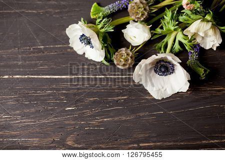 White anemones and white buttercups lying on old dark wood in the right top