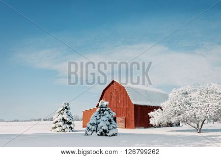 A rustic red Ohio barn covered in fresh snow with a bright blue sky background.
