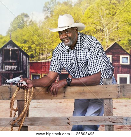 A mature African American cowboy happily looking at the viewer while leaning against a rustic rail fence and holding a gun.
