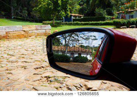 streets of the small brazilian historical town reflected at the car mirror