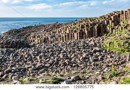 NORTHERN IRELAND, UK - AUGUST 03, 2015: Giants Causeway. Tourists visiting unique geological hexagonal formations of volcanic basalt rocks on Atlantic coast in County Antrim, Northern Ireland, UK, in sunset light. UNESCO World Heritage Site
