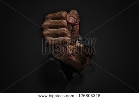 Power concept. Man fist punching through black paper