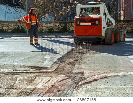 Worker checks traffic during the road surface milling work