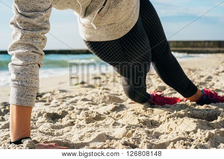 Girl in sportswear doing exercises on the beach in the morning