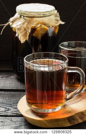 Traditional Russian drink kvass made from bread rye malt sugar and water. Kvass in the jug and mug on a dark wooden background. Selective focus