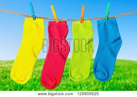 colorful socks hanging from a rope on the background field and sky