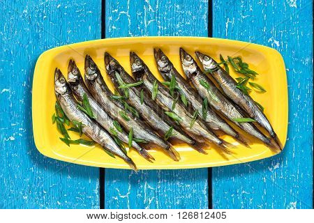 Smoked capelin with green onions on yellow plate on blue wooden background. Top view