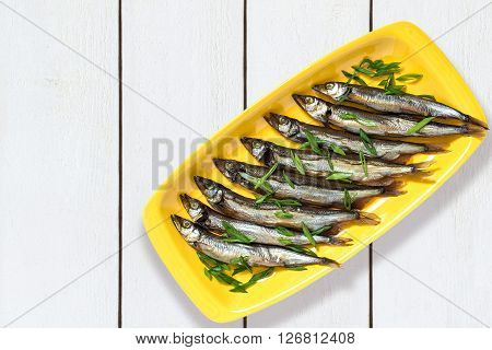 Smoked capelin with green onions on yellow plate on white wooden background. Top view