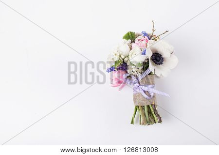 Spring bouquet from pink tulips violet grape hyacinths white anemones violet veronica and white buttercup with violet ribbon lying on white background