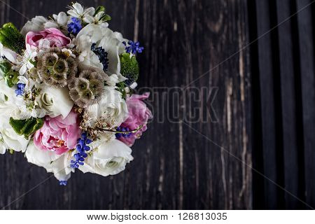 Bouquet from pink tulips violet grape hyacinths white anemones violet veronica and white buttercup with violet ribbon on black old wood and shutter from the top