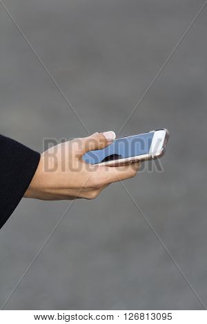 the girl in the arm with a French manicure keeps modern mobile phone on a grey background
