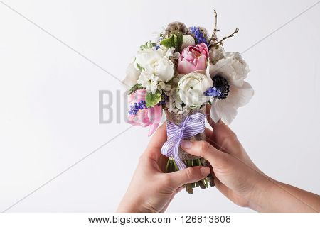 Two hands holding a spring bouquet from pink tulips violet grape hyacinths white anemones violet veronica and white buttercup with violet ribbon on the white background