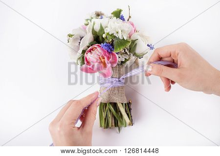 Two hands are making a bow from a violet ribbon in beautiful Easter bouquet from pink tulips violet grape hyacinths white anemones violet veronica and white buttercups on white background