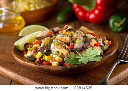 A delicious mexican style mussel salad with black beans cilantro red pepper jalapeno and corn.